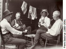 Four men sitting playing cards