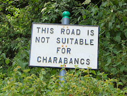An old road sign warning that a narrow road is unsuitable for charabancs.