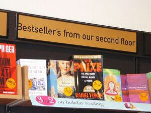 A photograph of a notice above a bookshelf, with the word 'Bestsellers' spelled with an intrusive apostrophe.